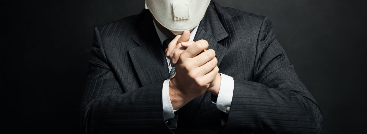 man in business suit wearing medical face mask